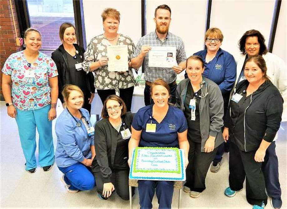 Members of the AMH stroke team celebrated their honor July 16 with pizza and cake in the hospital's café meeting rooms. The team includes staff from several departments, many of whom weren't present when the photo was taken. Front row left to right are Lindsay Middleton, Lindsay Crawford, Cassie Judkins (holding cake) and Alicia Gillean (all of the Intermediate Care Unit), and Beth Nevins of the Emergency Department. The back row includes, left to right, Marla Pearson and Tyler Spagnola of Radiology; Amy Schuler of Performance Improvement; stroke team coordinator Kyle Ogle; ED/Surgical Care Unit manager Cindy Bray; and Intermediate Care Unit manager Tammy Amizich.,