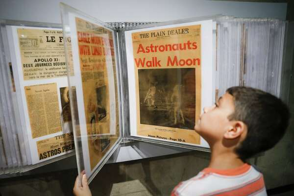 Ethan Reynolds browses a display of archival newspaper front pages announcing the first moon landing at the Armstrong Air & Space Museum as special events are underway for visitors commemorating the milestone's 50th anniversary, Saturday, July 20, 2019, in Wapakoneta, Ohio. (AP Photo/John Minchillo)