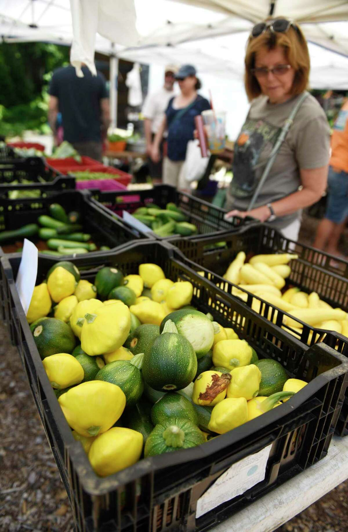 Customers browse the Smith's Acres stand at the Stamford Museum & Nature Center Sunday Farm Market in Stamford, Conn. Sunday, June 30, 2019.