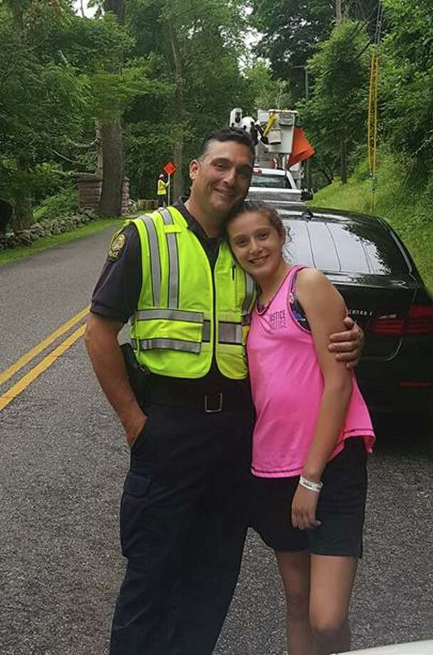 Ava Lombardo, of Newtown, with her dad, Lt. Robert Lombardo of the Greenwich Police Department. Ava will host a lemonade stand in Greenwich on Saturday to benefit the Catherine Violet Hubbard Animal Sanctuary in Newtown. Photo: Contributed /