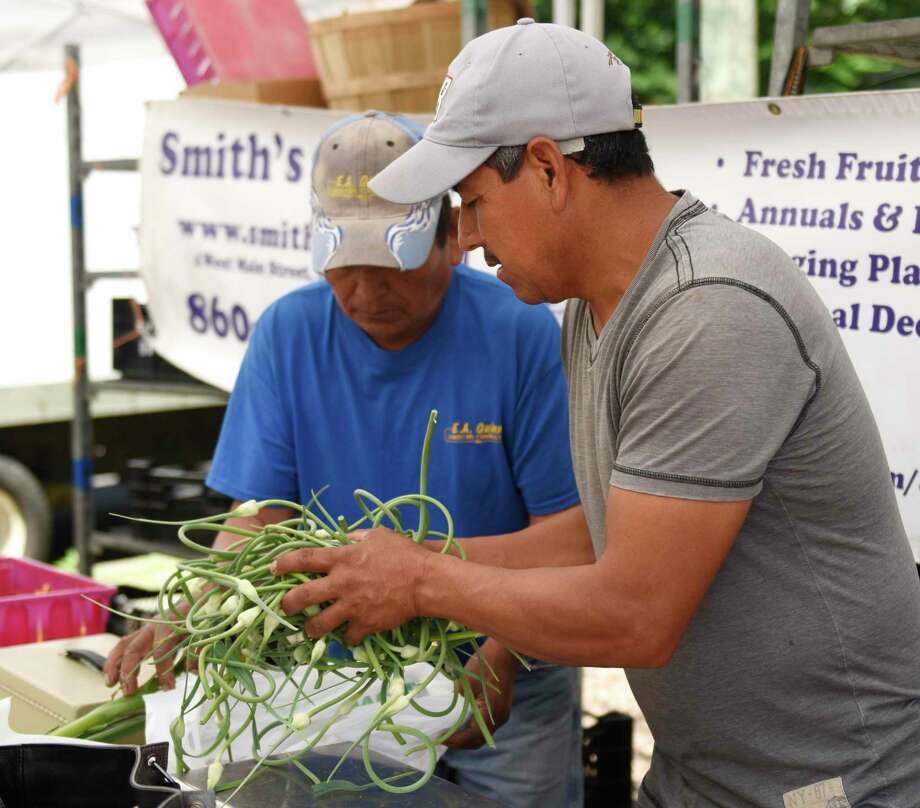 Smith's Acres workers Victorino Vasquez, left, and Guadaloupe Lopez weigh and bag veggies at the Stamford Museum & Nature Center Sunday Farm Market in Stamford, Conn. Sunday, June 30, 2019. Photo: File / Tyler Sizemore / Hearst Connecticut Media / Greenwich Time