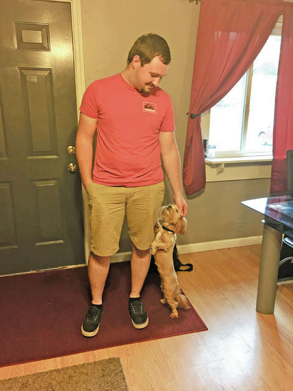 Blake Cruse, 21, stands with his girlfriend Nelly Porter's dog, Barracuda. Originally from Brighton, Cruse closed on a house on Lincoln Avenue in Jerseyville last year - a move he sees as a good investment. He also looked at homes in East Alton, Brighton and Delhi.