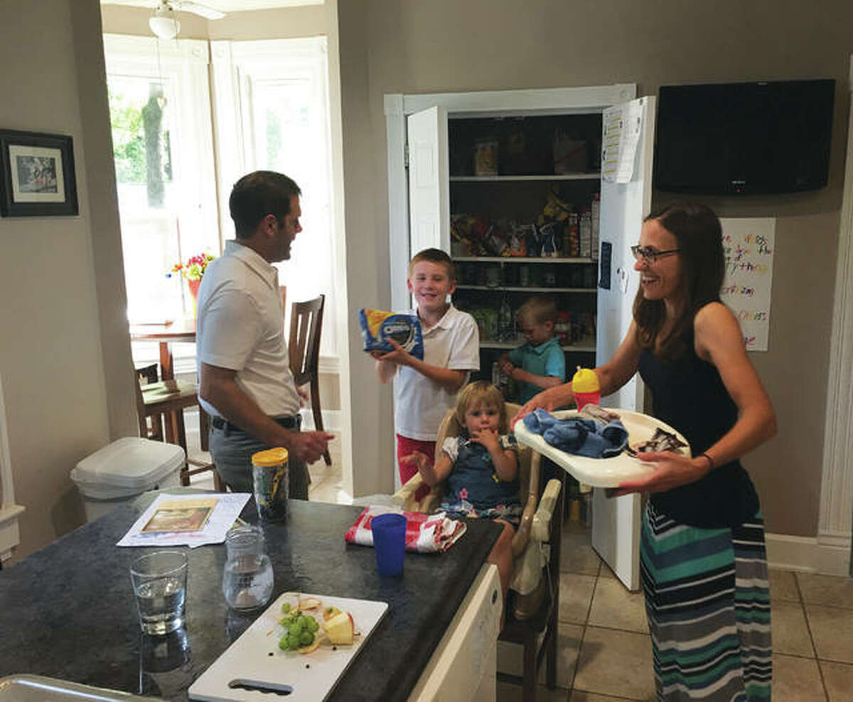John Cordes, left, talks to his son Joshua, 8, about an after-dinner snack, while his little brother, James, 7, looks through the kitchen pantry and their mother, Sarah Cordes, takes away the highchair tray from 1-year-old Mary at their Alton home on Henry Street.