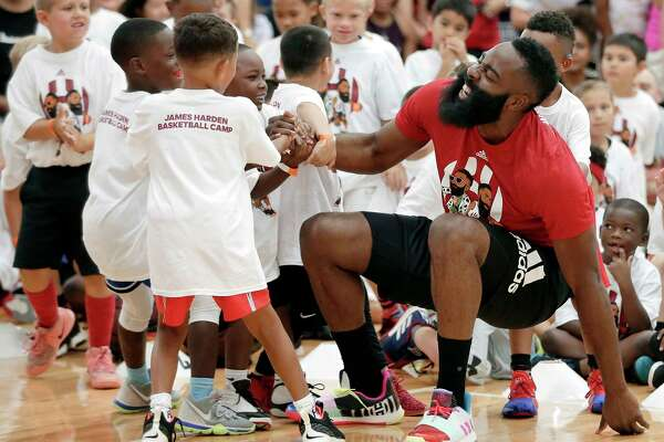 Houston Rockets' James Harden feigns an injury as he is helped up from the court after a fall by kids during a 20 second one-on-one game at the James Harden Basketball Camp held at the MI3 Center Saturday, Jul. 20, 2019 in Houston, TX.