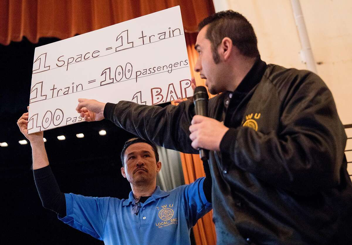 Local 250A and SFMTA train operations employees Ramon Galdamez (left) and Roger Marenco stand up to speak during a community meeting held at Balboa High School in San Francisco, Calif. Saturday, July 20, 2019 addressing the proposed safe parking center near the Balboa BART Station for people who are homeless and live in their cars. Transit operators oppose the project due to the loss of employee parking for SFMTA.