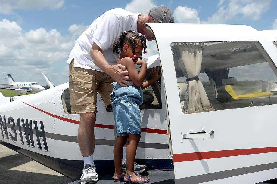 Pat Brown gives Tyah Dunes a closer view of his Comanche airplane during the Fly Beaumont Food Truck Day at the Beaumont Municipal Airport Saturday. Several small craft and helicopters flew in for the event, allowing spectators to get a close-up view of the planes and learn about them from their owners. Photo taken Saturday, July 20, 2019 Kim Brent/The Enterprise Photo: Kim Brent