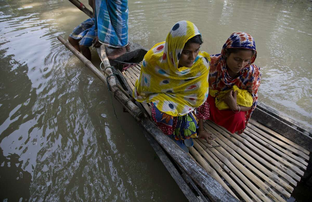 In this Friday, July 19, 2019 photo, Imrana Khatoon, left, rides a boat to get to a hospital, as a woman sits beside her holding Khatoon's newborn baby, in flood-affected Gagalmari, east of Gauhati, India. Khatoon, 20, delivered her first baby on a boat in floodwaters early Friday while on her way to a hospital, locals said. The woman and the newborn were brought back to their home without getting to hospital. They were however moved to a hospital on a boat to the nearby Jhargaon town because of unhygienic conditions due to floodwaters, Community health worker Parag Jyoti Das said. (AP Photo/Anupam Nath)