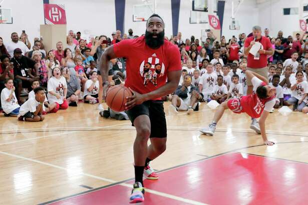 "Houston Rockets' James Harden goes up for a dunk past Youtuber ""Lost and Unbound"", right, during a 20 second one-on-one game at the James Harden Basketball Camp held at the MI3 Center Saturday, Jul. 20, 2019 in Houston, TX."