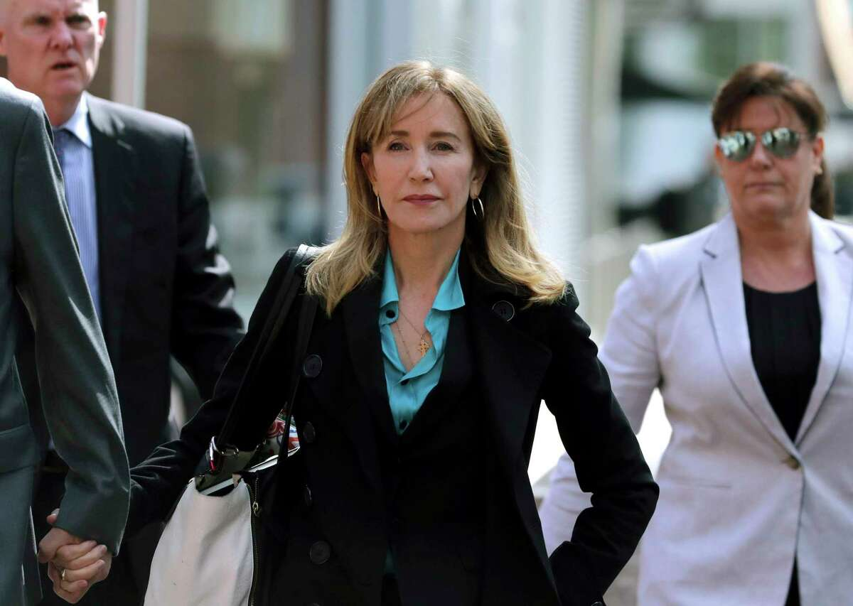 FILE - This April 3, 2019 file photo shows actress Felicity Huffman arriving at federal court in Boston to face charges in a nationwide college admissions bribery scandal. Huffman is facing a prison sentence after agreeing Monday to plead guilty to one count of conspiracy and fraud for paying a consultant $15,000 disguised as a charitable donation to boost her daughtera€™s SAT score. Prosecutors are seeking four to 10 months of confinement, and experts different on whether the plea, and Huffmana€™s subsequent apology taking full responsibility for her actions, will lead to a career rebound or retreat. (AP Photo/Charles Krupa, File)