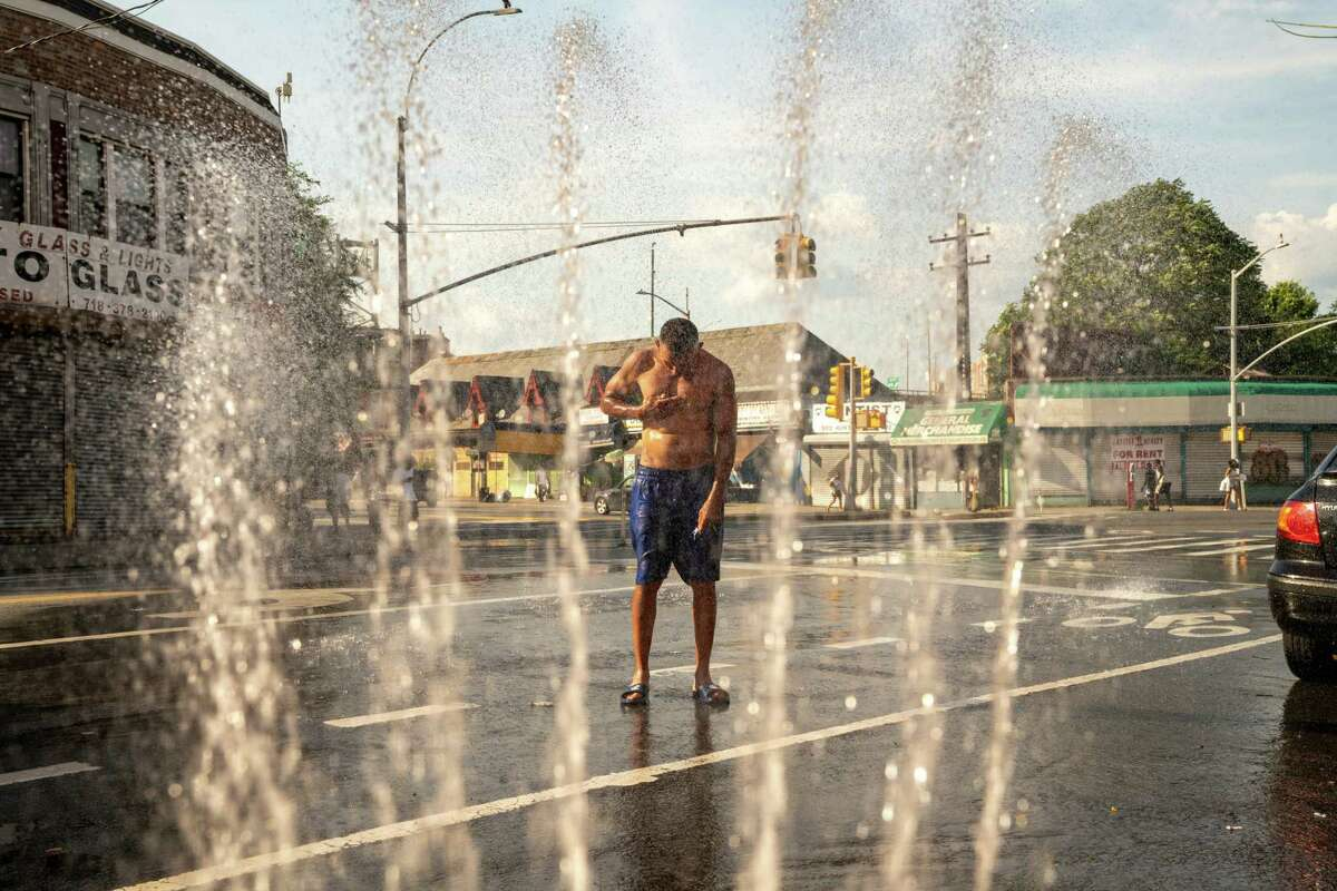 A person is sprayed with water from a fire hydrant in the Bronx borough of New York, U.S., on Saturday, July 20, 2019. Consolidated Edison Inc. is forecasting record power demand for New York this weekend as a heat wave blankets the city. Photographer: David 'Dee' Delgado/Bloomberg