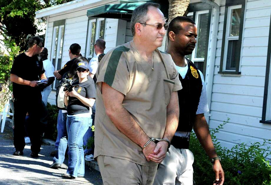 In this Feb. 2011 photo a DEA agent escorts Zvi Harry Perper to an awaiting police car after his Delray Pain Management clinic was raided by agents in Delray Beach, Fla.  Floridaa€™s a€˜pill millsa€™ were a gateway to the nationa€™s opioid crisis, feeding addiction and overdoses in Appalachia and other states. They exploded across Florida in the early 2000s and operated for years with little oversight. The release this week of July 19, 2019,  of a trove of federal data showing the distribution of opioids across the U.S. put the spotlight again on Floridaa€™s notorious a€˜pill mills,a€™ which provided the seeds of an epidemic that continues to cost tens of thousands of lives each year.  (Carline Jean/South Florida Sun-Sentinel via AP) Photo: Carline Jean / (C) 2011 Sun-Sentinel Company