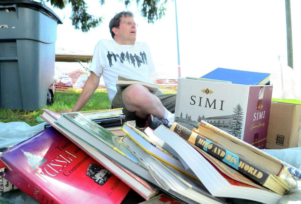 Doug Bonnell, of Southport, takes a break as he searches through a pile of books during the Westport Public Library's Annual Summer Book Sale on Jesup Green in Westport, Conn., on Saturday July 20, 2019. The sale continues Sunday, July 21: 10 am - 5 pm, Monday, July 22: 9 am -5 pm (Half-Price Day), and Tuesday, July 23: 9 am -1 pm ($5/Bag Day).