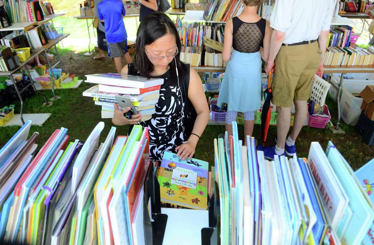 Jai Zhou, of Westport, searches to books for her children during the Westport Public Library's Annual Summer Book Sale on Jesup Green in Westport, Conn., on Saturday July 20, 2019. The sale continues Sunday, July 21: 10 am - 5 pm, Monday, July 22: 9 am -5 pm (Half-Price Day), and Tuesday, July 23: 9 am -1 pm ($5/Bag Day).