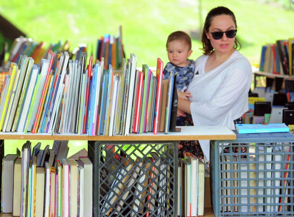 Busra Tuncoglu, of Haceksack, NJ, and her son Matthew, 6 mos, look around during the Westport Public Library's Annual Summer Book Sale on Jesup Green in Westport, Conn., on Saturday July 20, 2019. The sale continues Sunday, July 21: 10 am - 5 pm, Monday, July 22: 9 am -5 pm (Half-Price Day), and Tuesday, July 23: 9 am -1 pm ($5/Bag Day).