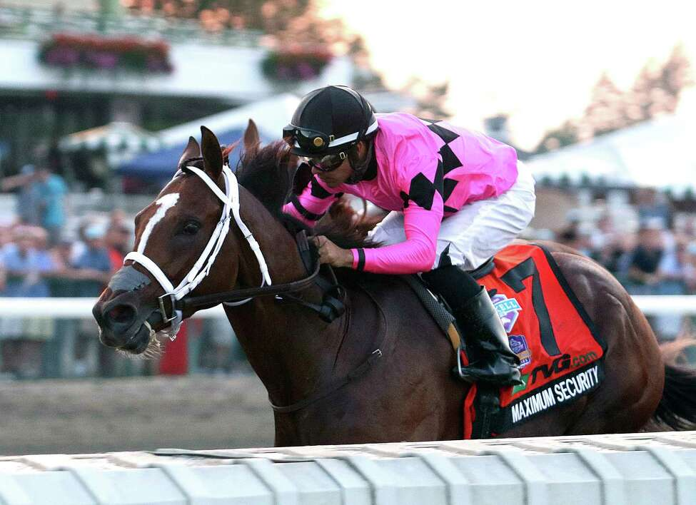 In this image provided by Bill Denver/EQUI-PHOTO, Inc., Maximum Security (7), ridden by Luis Saez, wins the Grade I - $1,000,000 TVG.com Haskell Invitational horse race Saturday, July 20, 2019, at Monmouth Park Racetrack in Oceanport, N.J. A new federal probe released Monday, March 9, 2020 has charged Maximum Security's trainer with illegal doping to enhance the horse's performance. (Bill Denver/EQUI-PHOTO, Inc. via AP)