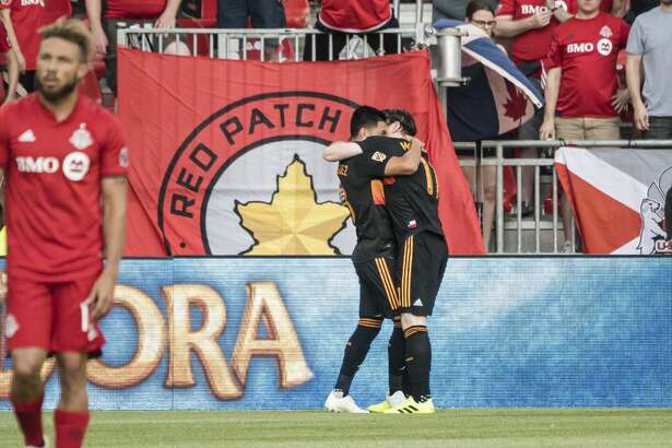 Houston Dynamo midfielders Tomas Martinez (10) and Thomas McNamara (11) celebrate after a goal during the first half of an MLS soccer game, Saturday, July 20, 2019 in Toronto. (Christopher Katsarov/The Canadian Press via AP)