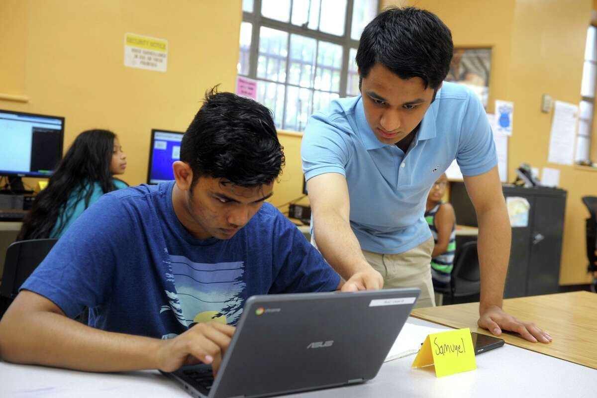 Nishant Wangneo, of Wilton helps Samuyec Islam, of Bridgeport, during a coding workshop that he teaches at the Burroughs-Saden Main Branch Library, in Bridgeport, Conn. July 19, 2019.