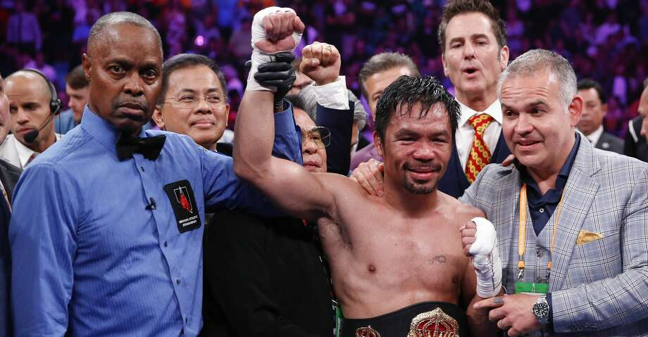 Manny Pacquiao, center, reacts as referee Kenny Bayless holds up his hand signaling his victory over Keith Thurman in a welterweight title fight Saturday, July 20, 2019, in Las Vegas. Pacquiao won by split decision. (AP Photo/John Locher) Photo: John Locher/Associated Press