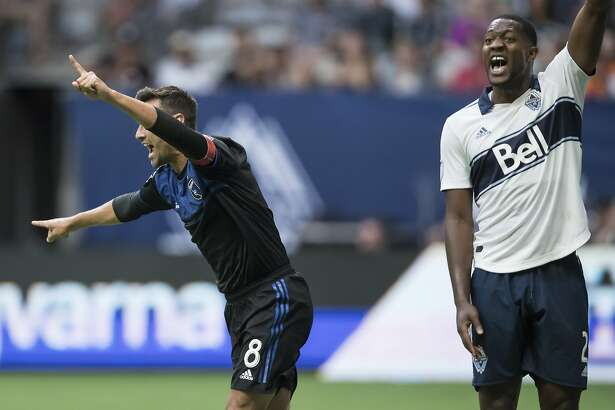 San Jose Earthquakes' Chris Wondolowski, left, celebrates his goal as Vancouver Whitecaps' Doneil Henry reacts during the first half of an MLS soccer match in Vancouver, British Columbia, Saturday, July 20, 2019. (Darryl Dyck/The Canadian Press via AP)