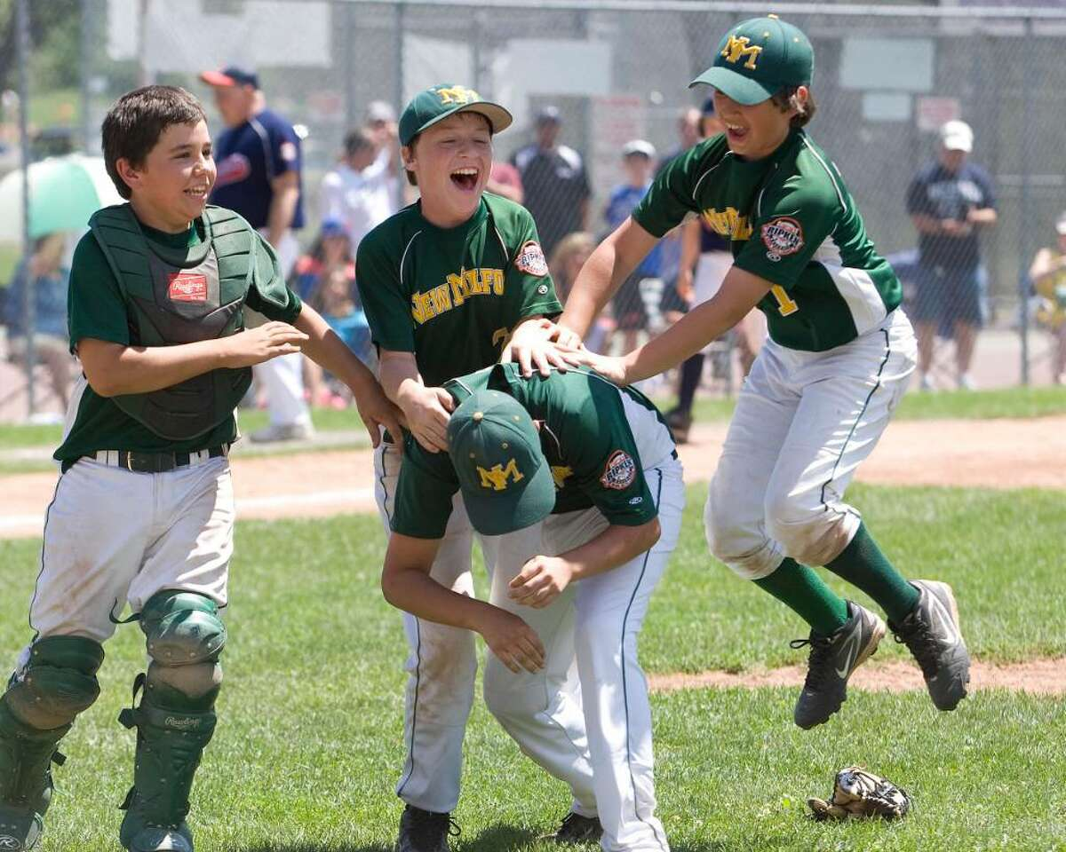 New Milford players, back row left to right, Robert Mosso, Brendan Profita and Tim Gesualdi celebrate with Tyler Hansen, who pitched the last three innings. New Milford defeated Danbury, 10-6, to win the Cal Ripken 11-year-old state tournament championship Saturday at Rogers Park.