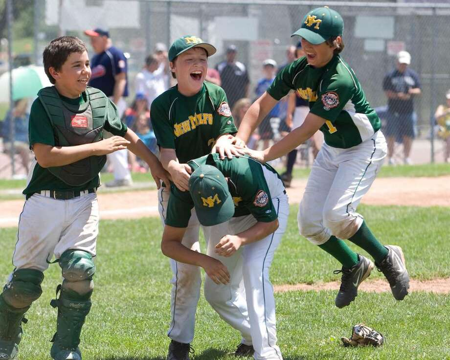 New Milford players, back row left to right, Robert Mosso, Brendan Profita and Tim Gesualdi celebrate with Tyler Hansen, who pitched the last three innings. New Milford defeated Danbury, 10-6, to win the Cal Ripken 11-year-old state tournament championship Saturday at Rogers Park. Photo: Barry Horn / The News-Times Freelance