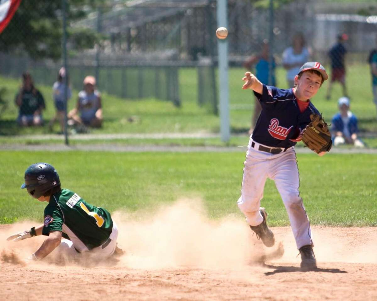 Danbury shortstop Eric Cerno turns a double play in the Cal Ripken 11-year-old state tournament championship game Saturday at Rogers Park. The play started with a hot shot at second baseman Brent Jacobellis. New Milford won, 10-6.