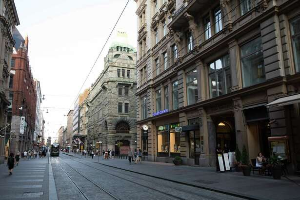 Pedestrians and a tram pass retail outlets along Aleksanterinkatu street in Helsinki, Finland, on July 16, 2018.
