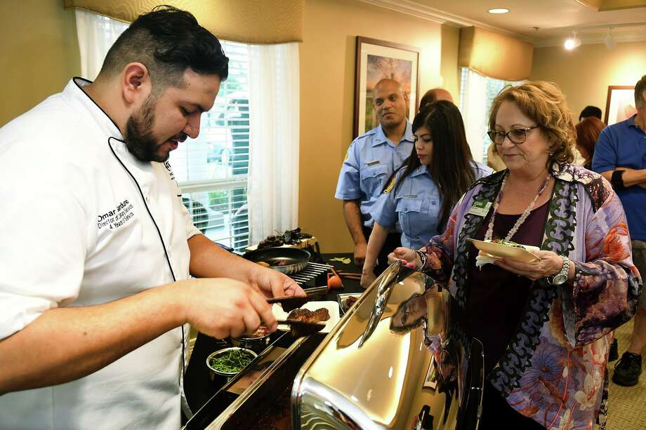 Chef Omar Garduno, left, Director of Culinary Services at Atria Kingwood, serves up some chicken with Mole sauce to Gina Koons, from right, Atria Sugar Land Executive Director, and Mari Benavente and her husband Alan Pagan, both members of the Klein Volunteer Fire Dept., as part of the Atria Cypresswood grand reopening and senior living community culinary showdown between four Atria chefs on July 18, 2019. Photo: Jerry Baker, Houston Chronicle / Contributor / Houston Chronicle