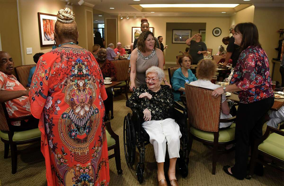 Celia Ramirez, center, a resident of Atria Cypresswood Senior Living in Spring, is all smiles as she navigates the dining area in her wheelchair, thanks to her daughter Sandi Murphy, as the pair joined the celebration of the center's grand reopening on July 18, 2019, after Hurricane Harvey.