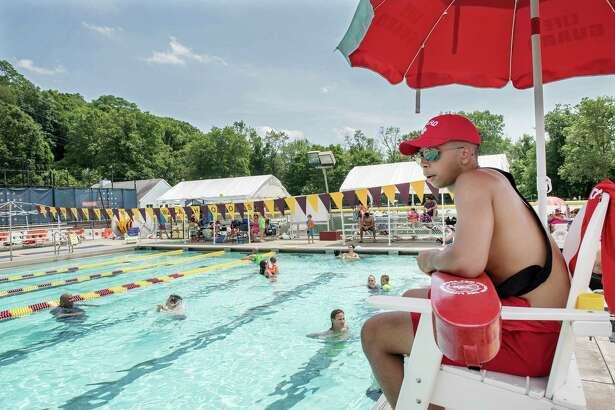 Wilton Y lifeguard Max Thors watches swimmers while they were getting relief from humid 94-degree day on Saturday at the Wilton YMCA pool.