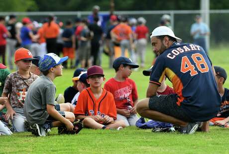Former Major League Baseball player Jarred Cosart, right, leads his group in a discussion of hitting fundamentals during the Legends for Youth Baseball Clinic at Legacy the School of Sports Sciences in Spring on July 19, 2019.