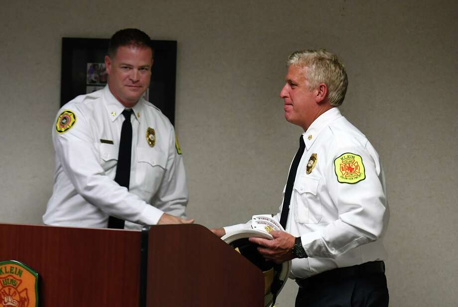 Mike Gosselin, right, is presented his official helmet after taking the oath of office as the Klein Volunteer Fire Dept.'s first full-time paid Fire Chief from Deputy Chief Eric Reinkemeyer during a ceremony at Klen Station 4 in Spring on July 20, 2019. Photo: Jerry Baker, Houston Chronicle / Contributor / Houston Chronicle