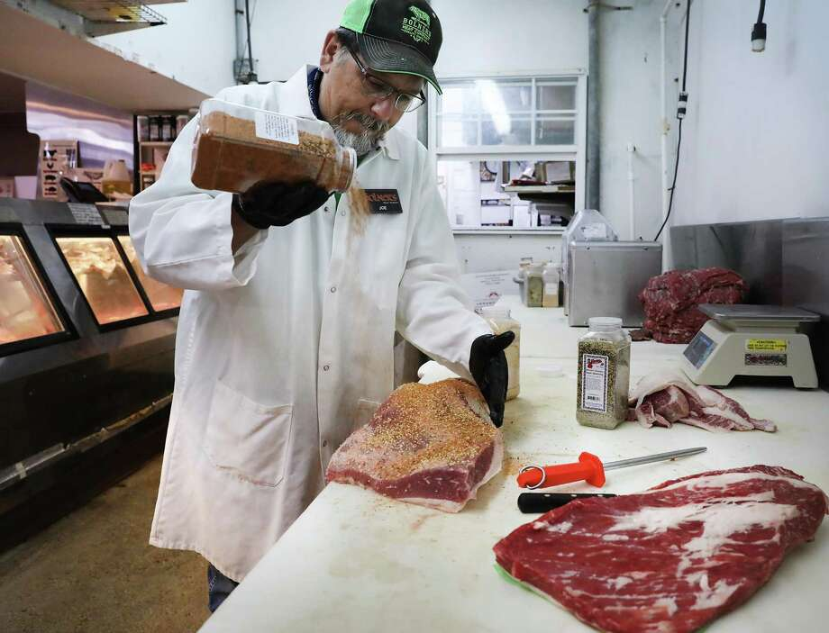 Joe Doria, manager at Bolner's Meat Market, applies seasoning as a dry rub to a brisket. He said that this year's brisket high season started early — before Memorial Day — and is going strong. Photo: Bob Owen / Staff Photographer / ©2019 San Antonio Express-News