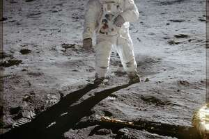 (1969-07-20) This photo is of Edwin Aldrin walking on the lunar surface. Neil Armstrong, who took the photograph, can be seen reflected in AldrinÕs helmet visor. Armstrong was the first human to ever stand on the lunar surface.