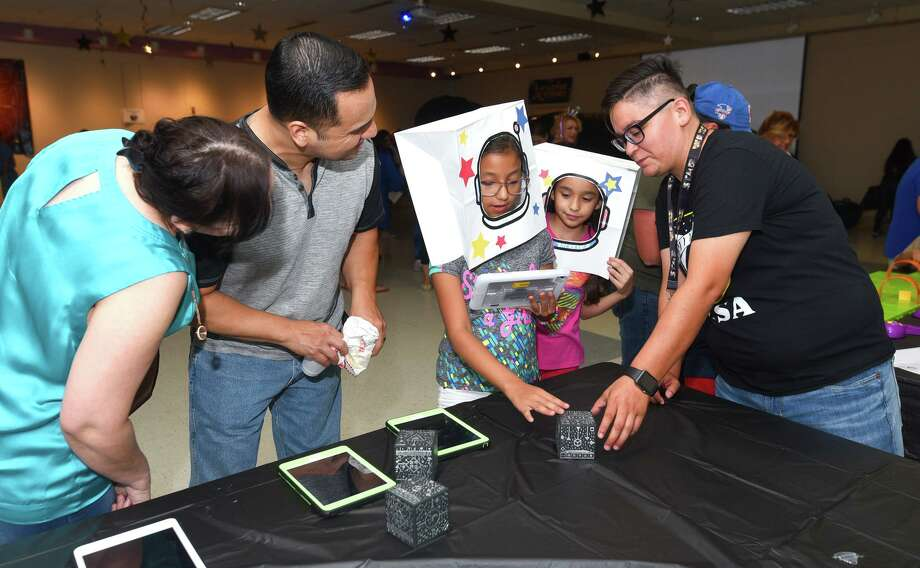 Ana Del Bosque, Frank Del Bosque, Genesis Del Bosque and Natalia Benavides learn about the solar system through an augmented reality app with the help of Niki Acosta Saturday at the Joe A. Guerra Laredo Public Library. Photo: Danny Zaragoza /Laredo Morning Times / Laredo Morning Times
