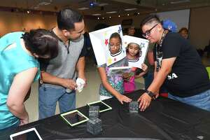 Ana Del Bosque, Frank Del Bosque, Genesis Del Bosque and Natalia Benavides learn about the solar system through an augmented reality app with the help of Niki Acosta Saturday at the Joe A. Guerra Laredo Public Library.