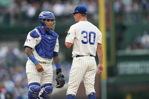 Chicago Cubs starting pitcher Alec Mills (30) and catcher Martin Maldonado meet on the mound during a rough first inning against the Cincinnati Reds on Tuesday, July 16, 2019 at Wrigley Field in Chicago, Ill.