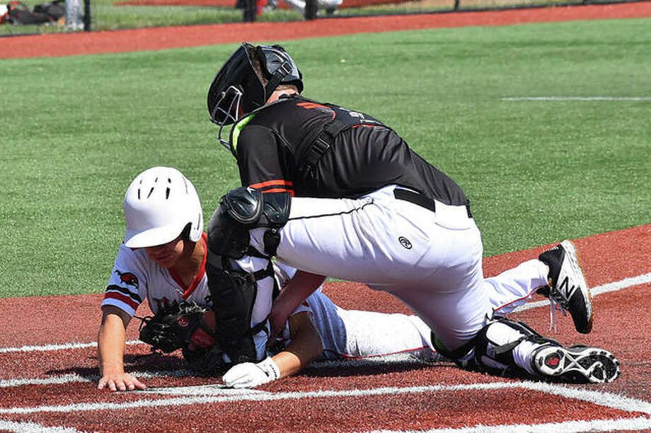 Edwardsville catcher Jacob Kitchen attempts to tag out the Hawks runner at the plate in the 10th inning. The runner was ruled safe. Photo: Matt Kamp|The Intelligencer