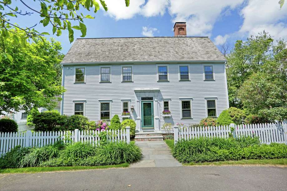 The gray reproduction colonial house at 45 Kellers Farm Road sits behind a Walpole picket fence and is located on a quiet cul-de-sac surrounded by gardens and protected lands.
