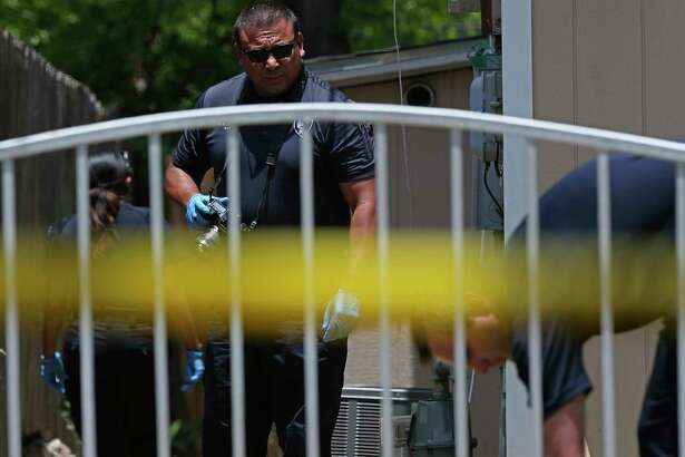San Antonio Police investigate the scene of a shooting at the 200 block of West Wildwood Drive, Sunday, July 21, 2019. A body covered with a yellow tarp was visible in the front yard of the residence.