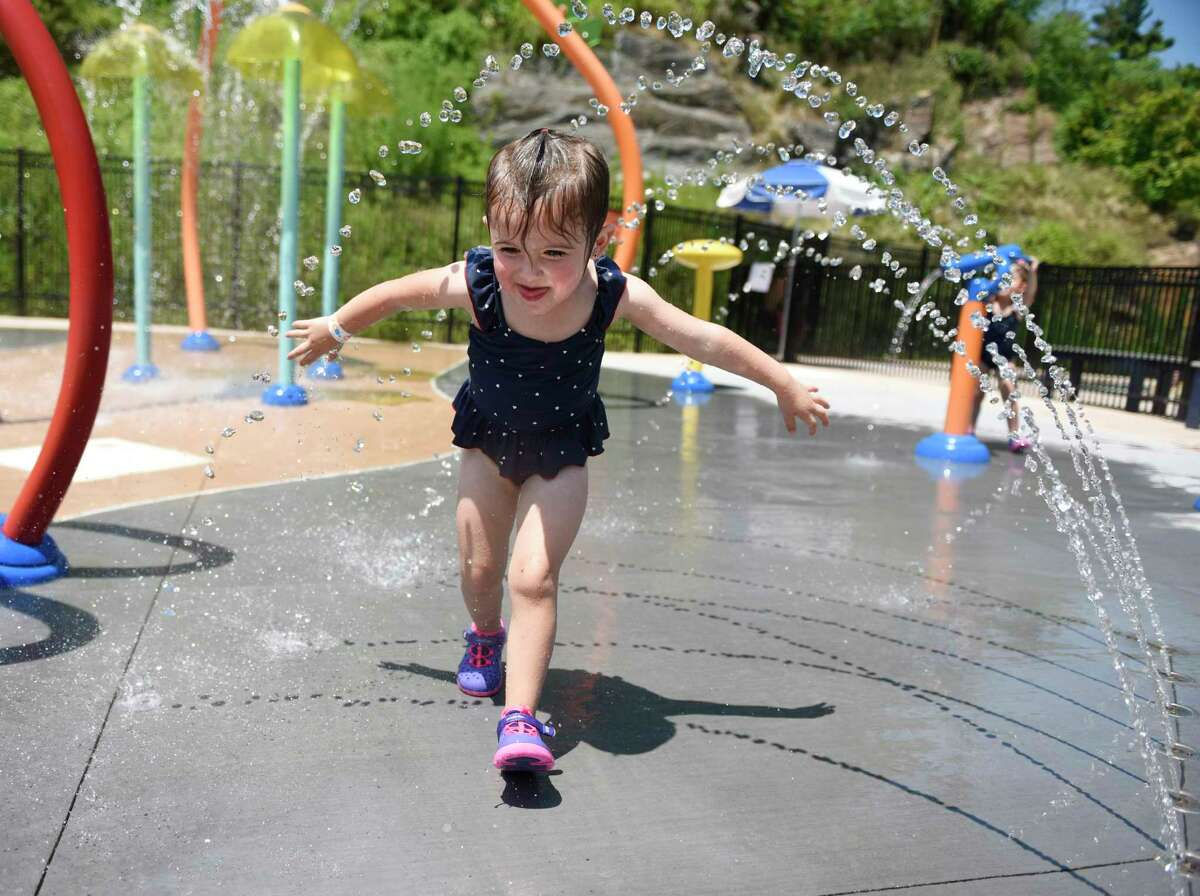 Byram's Charlotte Cummings, 3, runs through the splash pad at the Byram Pool in the Byram section of Greenwich, Conn. Sunday, July 21, 2019. Greenwich saw temperatures in the upper 90s over the weekend, but the heat is expected to break on Monday with an expected high in the upper 70s.