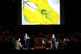 """The passionate relationship between painter Georgia O'Keeffe and photographer Alfred Stieglitz was depicted in a new orchestral song cycle with projected images on Saturday night at Tanglewood. Soprano Renee Fleming and baritone Rod Gilfry portrayed the famed lovers in """"The Brightness of Light"""" by composer Kevin Puts. Conductor Andris Nelsons led the Boston Symphony Orchestra in the world premiere performance in the Koussvitzky Music Shed. (Photo by Hilary Scott)"""