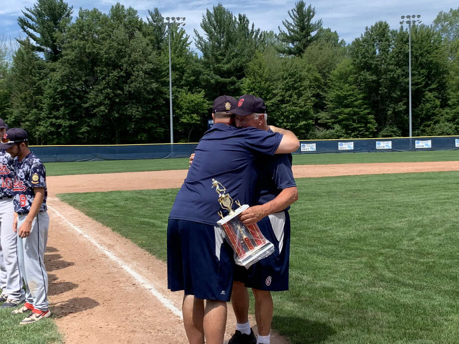 Gladwin Post 171 manager Terry Brokoff (right) is hugged by son and longtime assistant coach Scott Brokoff after Gladwin won the American Legion Baseball district/zone championship at Northwood on Sunday. Photo: Fred Kelly/fred.kelly@mdn.net