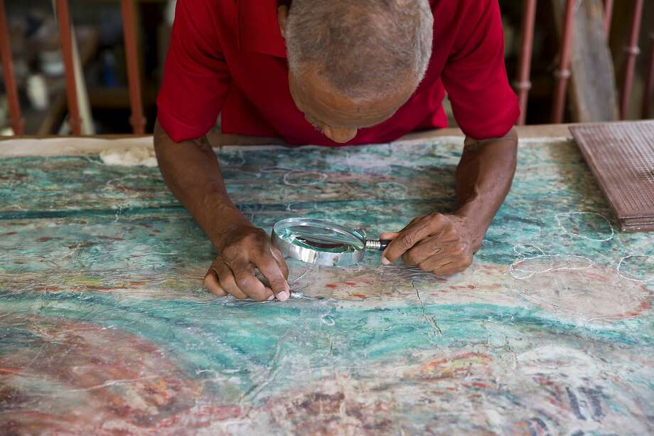 Artist Franck Louissaint works on the restoration of a work by painter Robert Saint-Brice at the Museum of Haitian Art of St. Pierre College in the capital of Port-au-Prince. Photo: Dieu Nalio Chery / Associated Press