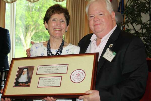 Virginia L. Golden, former president of St. Peter's and Albany Memorial Hospitals, poses with the 2019 Hope and Hospitality Award, after receiving it from Richard S. Zazycki, executive director and Mercy Associate of Circles of Mercy. (Photo by Sister Barbara Roman, RSM)