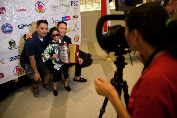 People pose with artists Samuel Miguel Redondo, center, and Junior Contreras, left, artists from Colombia at the Colombian Fest International? celebrates its 16th edition in Downtown Houston, Sunday, July 21, 2019.