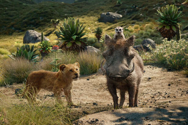 """FILE - This file image released by Disney shows, from left, young Simba, voiced by JD McCrary, Timon, voiced by Billy Eichner, and Pumbaa, voiced by Seth Rogen, in a scene from """"The Lion King."""" The Walt Disney Co. is ruling the box office again with the record-breaking debut of a€œThe Lion Kinga€ this weekend. The studio says Sunday, July 21, 2019 that the photorealistic remake devoured an estimated $185 million in ticket sales from 4,725 North American locations. Ita€™s a record for the month of July, PG-rated films and the ninth highest opening of all time.(Disney via AP, File)"""