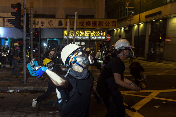 Demonstrators throw projectiles toward riot police during a standoff at a protest in the Sheung Wan district of Hong Kong on Sunday, July 21, 2019.