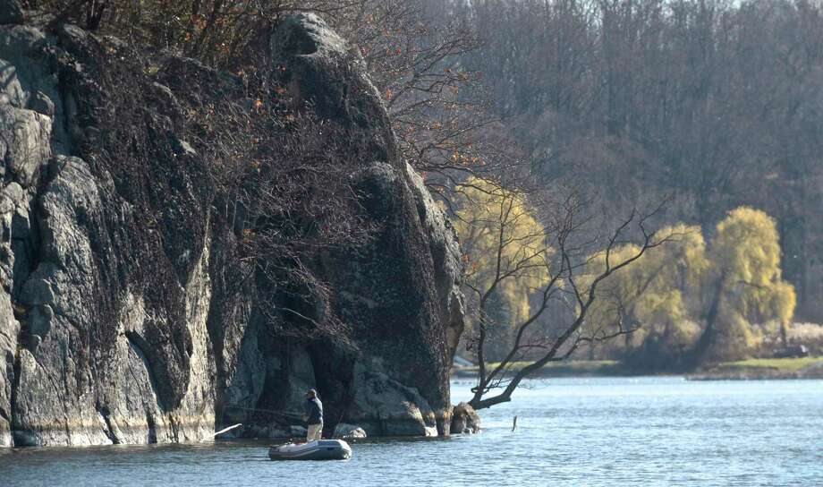 A fisherman tries their luck, early in the morning on a warm November day, on Mamanasco Lake under the cliffs of Richardson Park in Ridgefield, Conn. Photo: H John Voorhees III / Hearst Connecticut Media / The News-Times