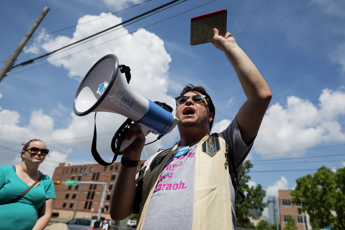 Rabbi Josh Fixler protests against the Southwest Key Detention Center on Emancipation Ave in Houston, Sunday, July 21, 2019. Fixler holds the Haggadah that belonged to his grandfather in Berlin. Never Again Is Now-Houston organized the protest against ICE and the detention center.